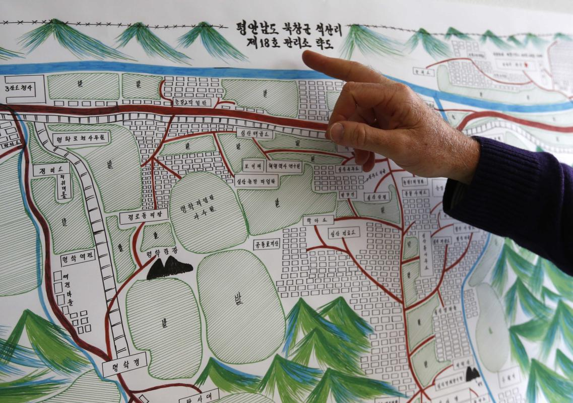 A U.N. Human Rights staff points to the title of a drawing describing North Korean labour camp no 18 in Geneva