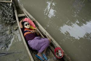 A resident rests in a boat floating in floodwaters …