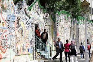 Syrians walk through a decorated wall that won the…