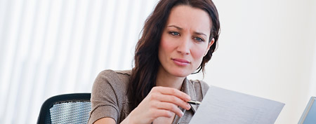 Young woman looking over resume (Corbis)