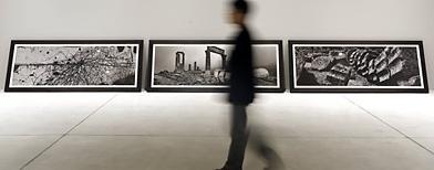 Un hombre pasa por una exposición de la Bienal de Venecia en su edición 2013/ Reuters