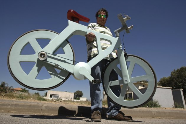 Israeli inventor Izhar Gafni holds his cardboard bicycle as he poses for a photo in Moshav Ahituv, central Israel September 24, 2012. The bicycle, made almost entirely of cardboard, has the potential to change transportation habits from the world's most congested cities to the poorest reaches of Africa, Gafni, an expert in designing automated mass-production lines and an amateur cycling enthusiast, says. Picture taken September 24, 2012. To match ISRAEL-CARDBOARDBIKE/     REUTERS/Baz Ratner (ISRAEL - Tags: ENVIRONMENT SPORT CYCLING SOCIETY)