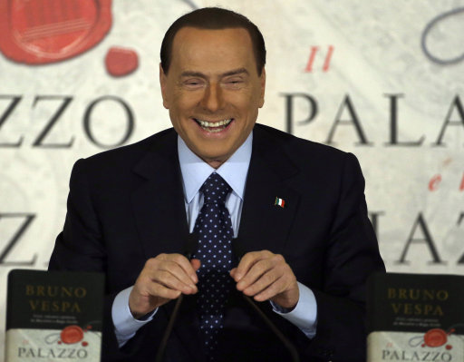 """FILE - In this Dec. 12, 2012 file photo Silvio Berlusconi smiles as he speaks during a book presentation of Italian journalist Bruno Vespa """"Il Palazzo e la Piazza"""" (The Palace and the Square) in Rome. Former Premier Silvio Berlusconi announced a deal Monday with the Northern League, his fractious coalition partner in three governments, to jointly run in Italy's election next month. The move could give fresh impetus to the center-right and extend the Berlusconi era. While leaving open the question of whether he will run himself, Berlusconi underlined his ambitions for the deal reached overnight at his villa near Milan by saying: """"Habemus Papum,"""", the Latin phrase for """"We have a pope."""" (AP Photo/Gregorio Borgia, File)"""