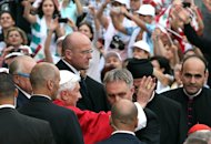 Pope Benedict XVI, center left, arrives surrounded by security guards at St. Paul's Basilica in Harissa, Lebanon, near Beirut, where he will stay at the Vatican embassy, Friday, Sept. 14, 2012. Benedict arrived in Lebanon on Friday to urge peace at a time of great turmoil in the Middle East region. (AP Photo/Hussein Malla)