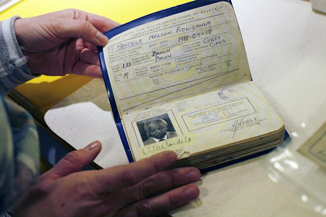 "In this image taken Friday June 14, 2013, A Mandela Foundation employee shows the archived passport of former South African President Nelson Mandela. Nelson Mandela's condition in a Pretoria hospital remained critical for a second straight day Monday June 24, 2013, said South Africa's president Jacob Zuma, who described the stricken anti-apartheid hero as being ""asleep"" when he visited him the previous evening.(AP Photo/Jerome Delay)"