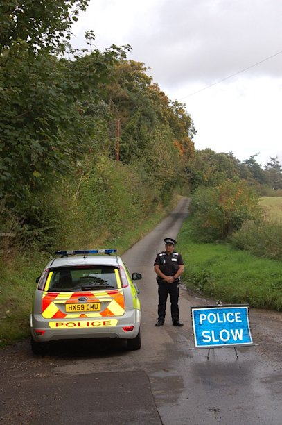 A police officer guarding the closed off bridleway in Newton Stacey where the bodies of a man and two children were found