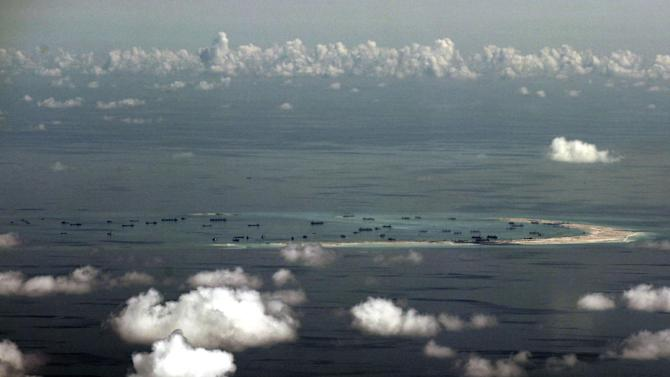 "FILE - In this May 11, 2015, file photo, this aerial photo taken through a glass window of a military plane shows China's alleged on-going reclamation of Mischief Reef in the Spratly Islands in the South China Sea. China will complete land reclamation projects on its disputed South China Sea territorial claims as planned within ""upcoming days,"" the Foreign Ministry said Tuesday, June 16, 2015. (Ritchie B. Tongo/Pool Photo via AP)"