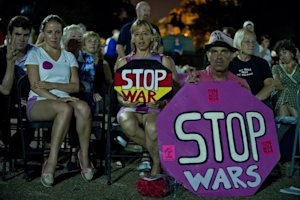 Demonstrators opposed to US intervention in Syria listen …