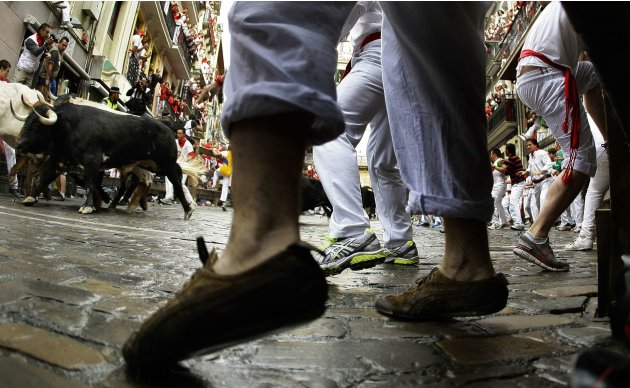 A Dolores Aguirre fighting bull passes runners at the Estafeta corner during the first running of the bulls of the San Fermin festival in Pamplona