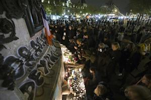 People light candles at a memorial in tribute of Paris bombing