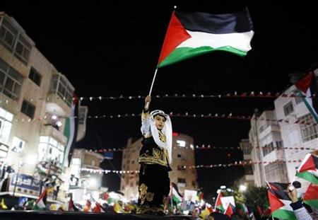 "A Palestinian boy in traditional clothes waves a Palestinain flag during a rally in the West Bank city of Ramallah November 29, 2012. Palestinian President Mahmoud Abbas appealed to the U.N. General Assembly to recognize Palestinian statehood by supporting a resolution to upgrade the U.N. observer status of the Palestinian Authority from ""entity"" to ""non-member state."" REUTERS/Marko Djurica"