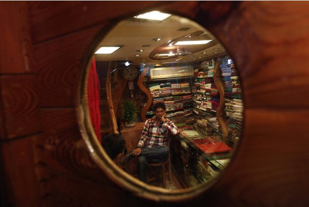 A shop attendant is pictured through a decorative window in his retail shop as he waits for customers in Mumbai