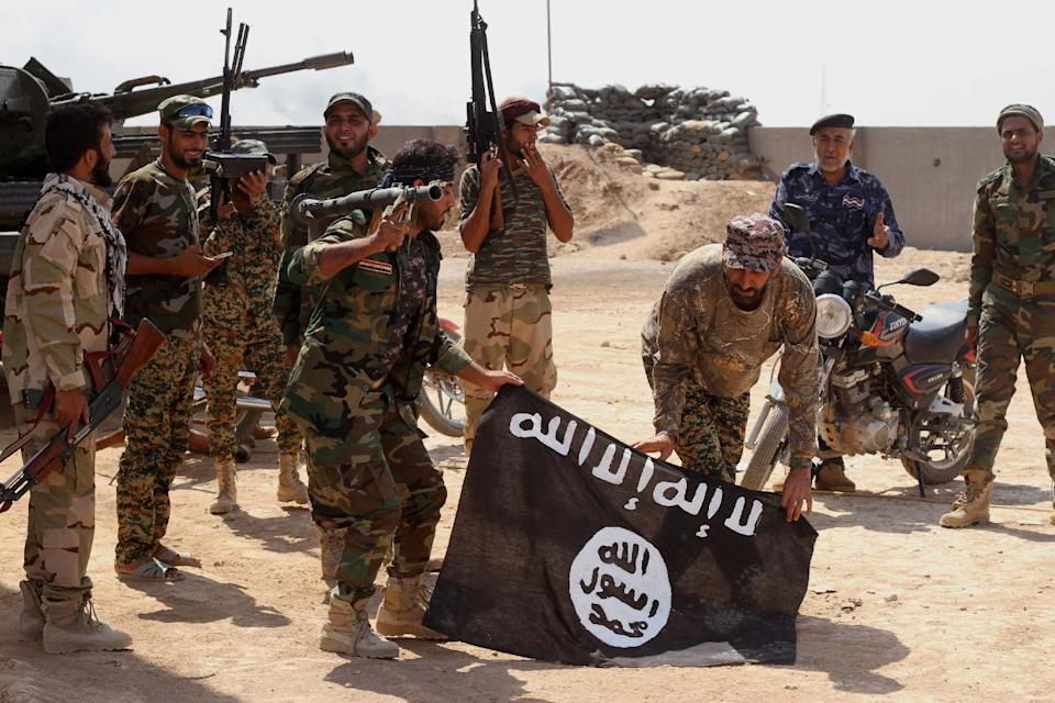 FILE - In this Tuesday, Oct . 7,  2014  file photo, Iraqi security forces hold a flag of the Islamic State group they captured during an operation...