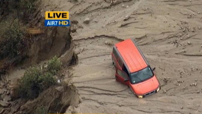 This image taken from video provided by KABC-TV, shows a vehicle stuck along a muddy road in the mountainous community of Green Valley, Calif., about 65 miles northwest of downtown Los Angeles on Thursday, Oct. 15, 2015. Flash flooding in northern Los Angeles County has filled several roads with mud, stranding vehicles and blocking traffic on one of the state's main highways. (KABC-TV via AP) MANDATORY CREDIT; TV OUT