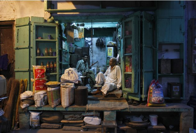 A shopkeeper and his sales assistant wait for customers inside a family-owned grocery store in an alley in the old quarters of Delhi