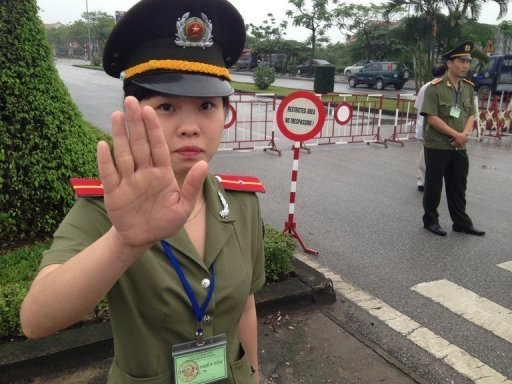 A Vietnamese policewoman stops reporters outside the People's Court House in Hai Phong, on April 2, 2013