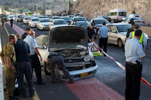Israeli police inspect the damaged car of a Palestinian…