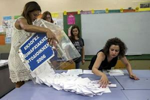 A ballot box is emptied by a voting official at the…