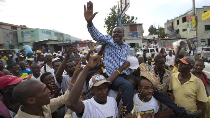 In this Oct. 17, 2015 photo, presidential candidate Moise Jean Charles, of the Platform Pitit Dessalines political party, is carried by supporters as he campaigns in Port-au-Prince, Haiti. This year's unprecedented three rounds of balloting will pick Haiti's next president, two-thirds of the Senate, the entire Chamber of Deputies and local offices. The Oct. 25 vote is expected to clear the sprawling presidential field for a runoff Dec. 27 between the top two finishers. (AP Photo/Dieu Nalio Chery)