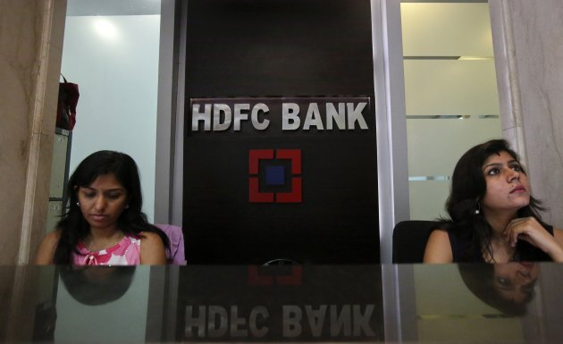 Personal bankers wait for customers at the reception of a HDFC Bank branch in Mumbai
