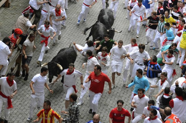 A runner is lifted by his scarf onto the horns of a Dolores Aguirre fighting bull on the the first day of the running of the bulls in Pamplona