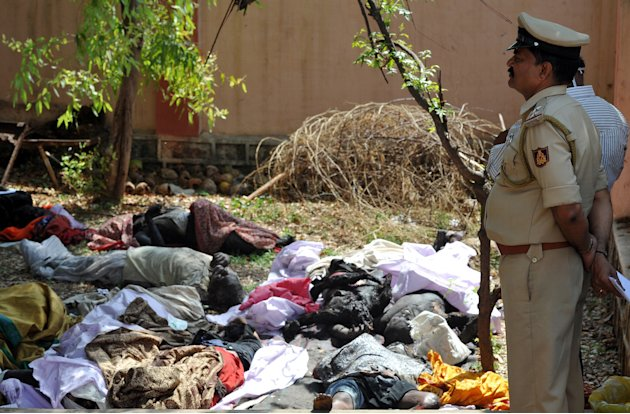A police officer at the mortuary of Pennukonda District Hospital looks at the burnt bodies of victims of the collision between the Bangalore-bound Hampi Express and a stationary goods train, at Pennec