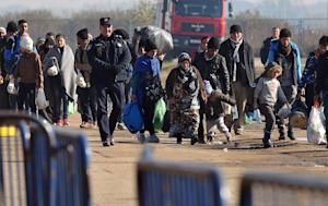 A Croatian policeman escorts migrants and refugees …