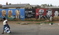 FILE - In this Dec. 11, 2012 file photo, a woman walks past a mural depicting portraits of former South African President Nelson Mandela in Soweto, South Africa. The chipped street mural depicts stations in the life of Mandela each matched by a portrait of the global icon as he advanced from robust youth to old age. Now this infirm giant of history faces a struggle with mortality, it's duration unknown but its outcome certain. (AP Photo/Themba Hadebe, File)