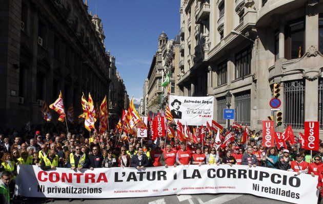 """People hold banners and placards as they march during a protest against government austerity measures in Barcelona March 10, 2013. The banner reads """"Against unemployment and corruption"""". REUTERS/Albert Gea (SPAIN - Tags: CIVIL UNREST BUSINESS EMPLOYMENT POLITICS)"""