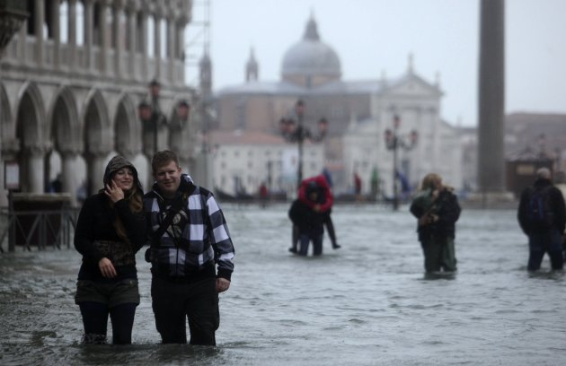 People walk through a flooded street during a period of seasonal high water in Venice