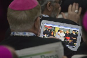 A bishop watches live video on his tablet of Pope Francis …