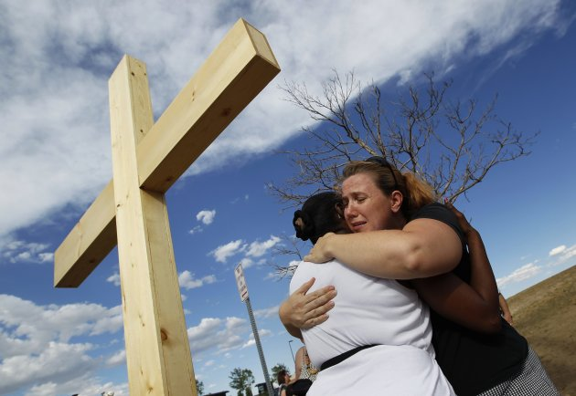 """Naomi Hicks (R) hugs a woman at a memorial for victims, behind the theater where a gunman opened fire on moviegoers in Aurora, Colorado July 21, 2012. James Holmes, the suspect accused of a shooting rampage at a Denver- area premiere of the new """"Batman"""" film, received a high volume of deliveries at work and home over the past four months, police said, parcels they believe contained ammunition and possibly bomb-making materials. REUTERS/Shannon Stapleton (UNITED STATES - Tags: CRIME LAW SOCIETY CIVIL UNREST OBITUARY TPX IMAGES OF THE DAY)"""
