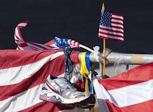 A running shoe and US flag is pictured at a memorial…
