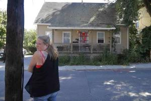 A local resident stands across the street from a home…