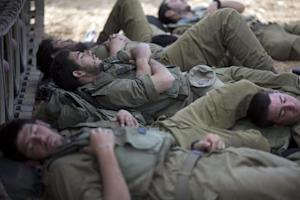 Israeli soldiers sleep in the shade of a military vehicle …