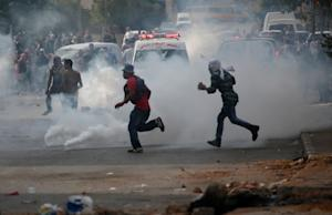Palestinian protesters run through tear gas in clashes …