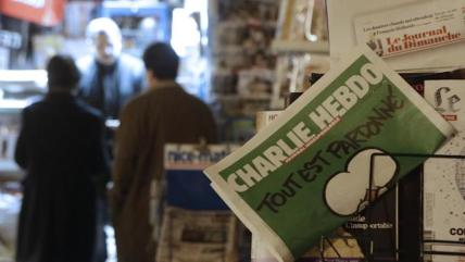 "Charlie Hebdo newspaper is displayed at a newsstand in Nice southeastern France, Wednesday, Jan. 14, 2015. On front page, reading ""All is forgiven"". Charlie Hebdo's defiant issue is in print, with a caricature of the Prophet Muhammad on the cover and a double-page spread claiming that more turned out Sunday to back the satirical weekly ""than for Mass."" Twelve people died when two masked gunmen assaulted the newspaper's offices on Jan. 7, including much of the editorial staff and two police. (AP Photo/ Lionel Cironneau)"