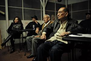A group of Hispanic people watch a television broadcast…