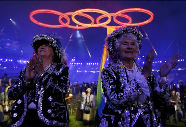 Performers clap as the Olympic rings are seen above, during the opening ceremony of the London 2012 Olympic Games at the Olympic Stadium