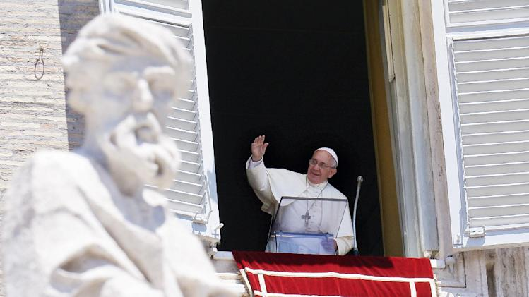 Pope Francis waves during his Sunday Angelus from the window of his study overlooking St.Peter's Square at the Vatican on July 6, 2014