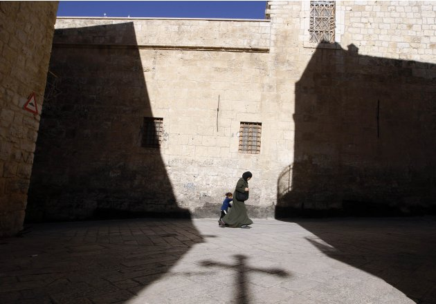 A file picture shows a Palestinian woman walking with a child past a shadow of a cross cast by the Church of the Nativity in Bethlehem