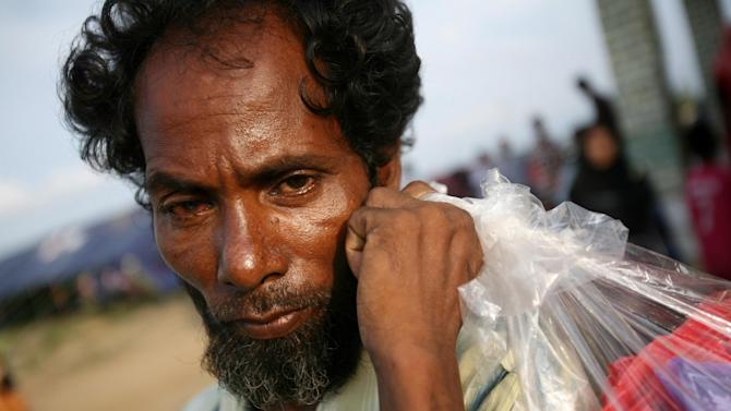 An ethnic Rohingya man carries a plastic bag containing his belongings at a temporary shelter in Lapang, Aceh province, Indonesia, Thursday, May 14, 2015. More than 1,600 migrants and refugees from Myanmar and Bangladesh have landed on the shores of Malaysia and Indonesia in the past week and thousands more are believed to have been abandoned at sea, floating on boats with little or no food after traffickers literally jumped ship fearing a crackdown. (AP Photo/Binsar Bakkara)