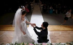 Groom puts a wedding ring on his bride's finger during a wedding ceremony at a budget wedding hall at the National Library of Korea in Seoul, South Korea