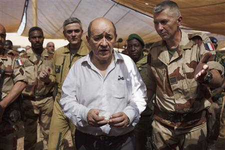 France's Defence Minister Jean-Yves Le Drian (C) speaks to a French soldier at a French military encampment at a Malian air base in Gao March 7, 2013. Le Drian paid a surprise visit on Thursday to French forces battling Islamist rebels in rugged northern Mali, saying their military mission would not end until security was restored in the West African country. REUTERS/Joe Penney