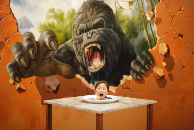Girl poses for a photograph in front of a 3D painting at the 2012 Magic Art Special Exhibition in Hangzhou