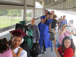 Wearing graduation-style cap and gown, U.S.-raised …