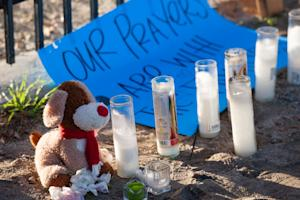 A stuffed animal, candles and a sign are part of a …