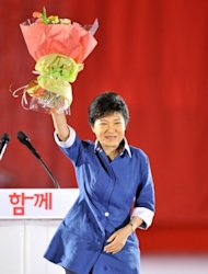 "Park Geun-Hye (centre), the daughter of assassinated dictator Park Chung-Hee, after she was elected as a presidential candidate in a primary held by the New Frontier Party in Goyang, north of Seoul, on August 20. Beaming broadly, Park accepted a bouquet of flowers from party leaders and promised to secure the presidency and create a country ""full of dreams and hope"". (AFP Photo/Jung Yeon-Je)"
