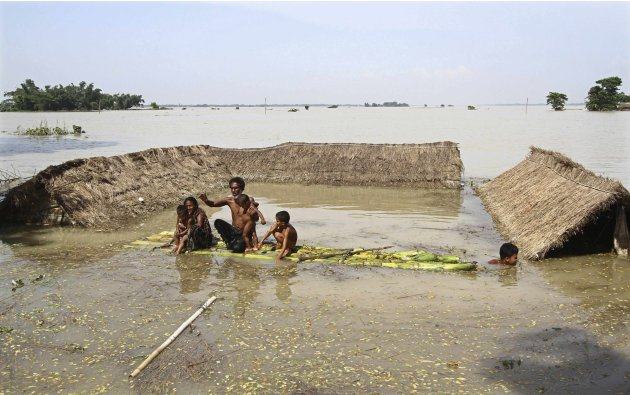 Flood-affected residents move to safer places on a temporary raft next to their submerged huts after heavy rains at Khalabhyan village