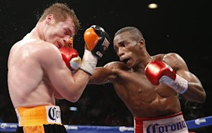 Canelo Alvarez (left) takes a hit from Erislandy Lara. (AP)